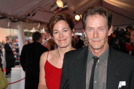 Stephen McHattie and Lisa Houle together at a party. Lisa is in red while Stephen is wearing a suit.